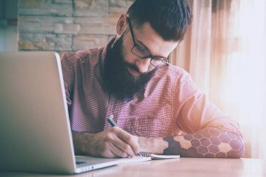 Bearded man working with laptop