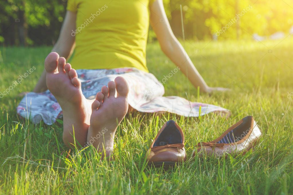 girls legs lying in grass barefoot