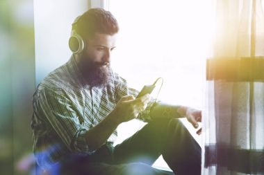 bearded man in headphones listening music