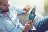 Lächelnder Geschäftsmann mit digitalem Tablet und Kopfhörern telefoniert mit Videokonferenz