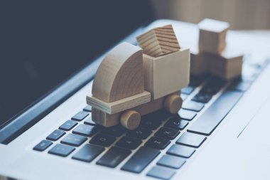 Wooden toy truck on laptop keyboard. Internet shopping, on-line purchase, e-commerce and packages delivery concept.