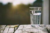 Fotografia Bicchiere di acqua pura su priorità bassa di alba naturale con lo spazio della copia