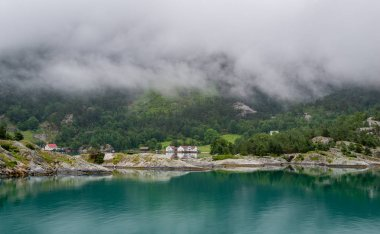 Houses of norwegian village at fjords shores .