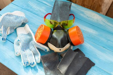 Abrasives, sansing paper and sanding sponges and sanding wheel respirator on the blue wooden background close up
