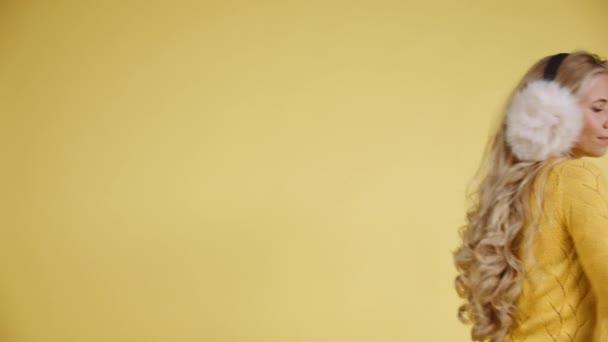 Ein aufgepupptes Model trägt ein gelbes Top und einen flauschigen Ohrenschützer, der rückwärts tanzt