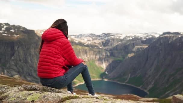 Frau in roter Jacke bewundert die Aussicht auf einen Berg