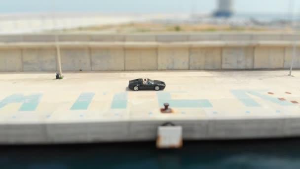 Black Ferrari Coasting by the Docks at Day