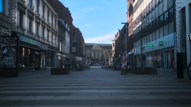 Zaparkovaná kola podél prázdné ulice obklopené uzavřenými obchody