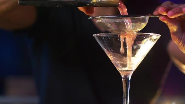 Männlicher Barkeeper im Hintergrund schenkt Cocktail-Drink in Zeitlupe ein