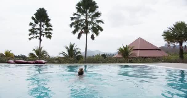 Blick auf die Hütte und die Natur mit einer am Pool schwimmenden Frau