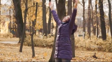 Happy young pretty brunette woman throws the autumn leaves in the park.