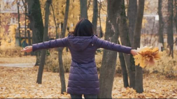 Šťastná mladá bruneta žena točí s podzimní listí v parku.