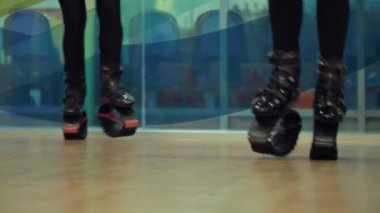 Four people jumping in kangoo shoes in the gym.