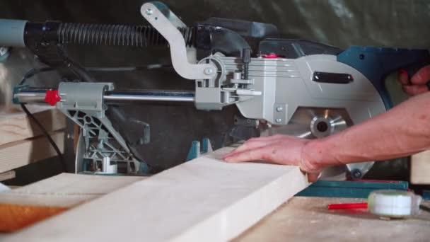 Dělník řeže prkno s kruhovou pilou.