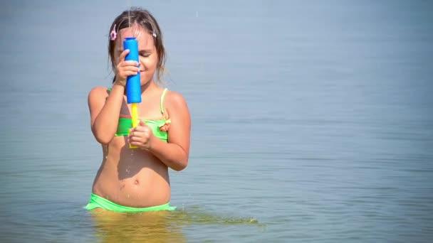 malá dívka hraje s vodou