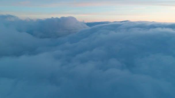 Letecký pohled na magicky modré kumulující se mraky se při západu slunce usadil na obloze. Zimní sníh, olověné mraky nahromaděné proti zapadajícímu slunci