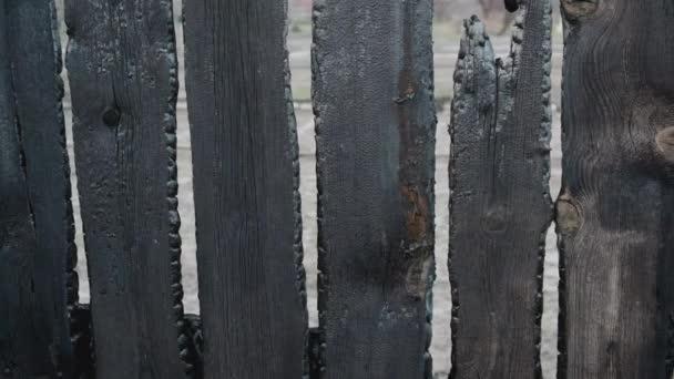 Spálené ploty po požáru v soukromém domě. Důsledky neopatrného a bezohledného zacházení s ohněm. 4K UHD videokamera