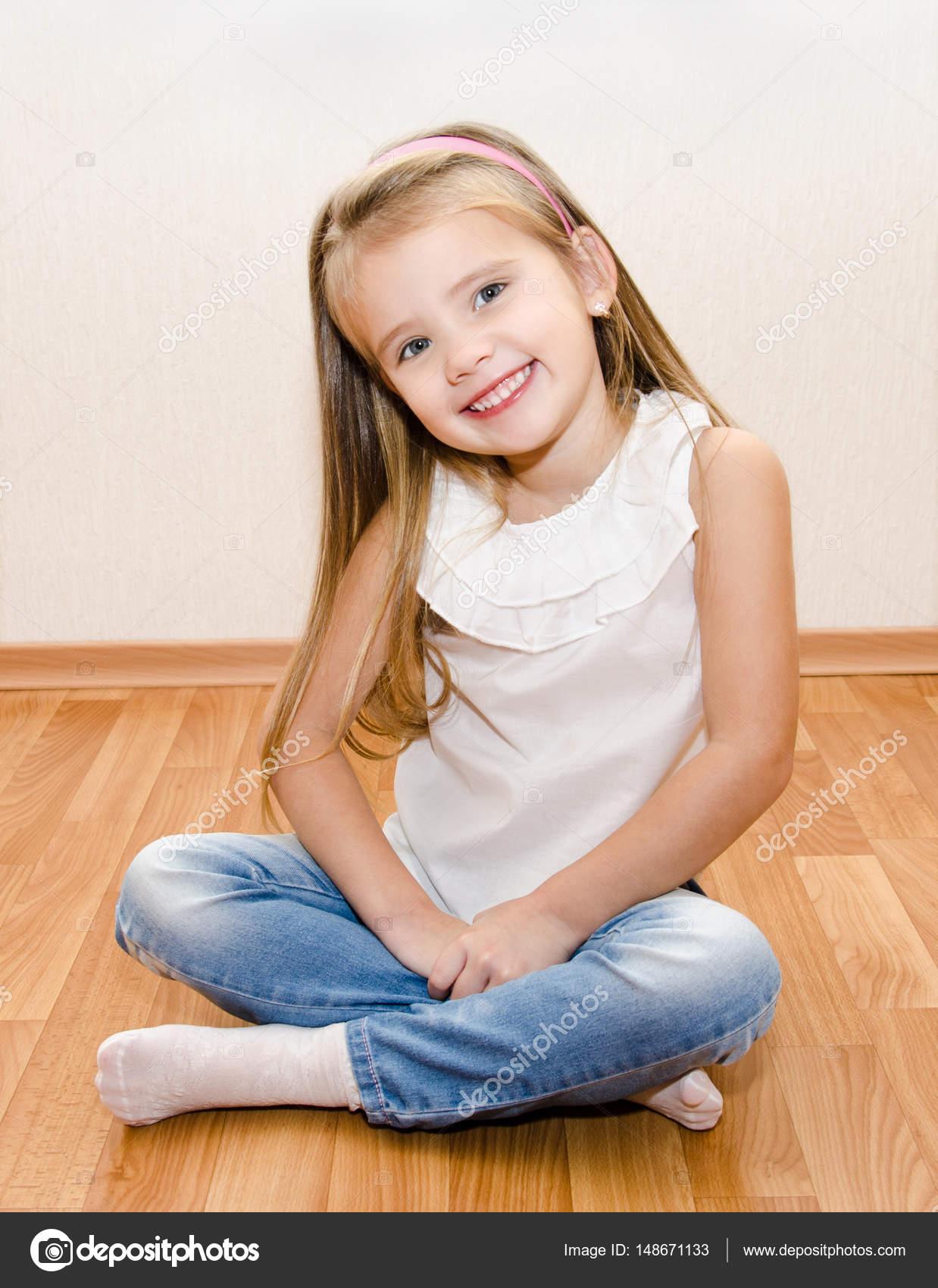 Smiling Cute Little Girl Sitting On Floor
