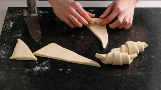 Egy női pék sütés előtt gyönyörű croissant-t csinál. Házi készítésű, friss, ízletes süteményes zsemle és croissant. Hagyományos olasz családi pékség.
