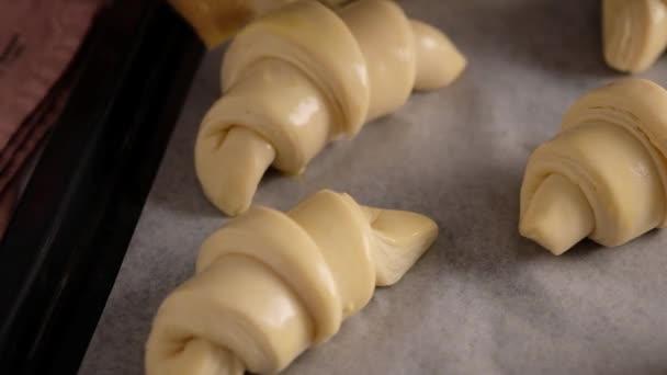 Samice pekařky před pečením mění krásné croissanty. Domácí čerstvé chutné pečivo a croissanty. Tradiční italská rodinná pekárna. Zpomalené jídlo.