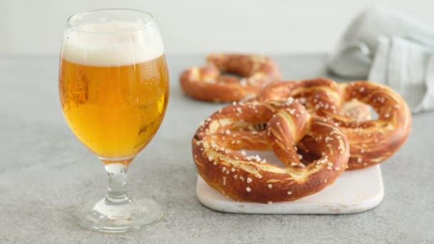 Oktoberfest food menu, soft pretzels and beer on a wooden board and white background. Beer is poured. Misted glass with beer. Female hands take britzel.
