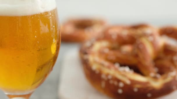 Oktoberfest food menu, soft pretzels and beer on a wooden board and white background. Beer is poured. Misted glass with beer.