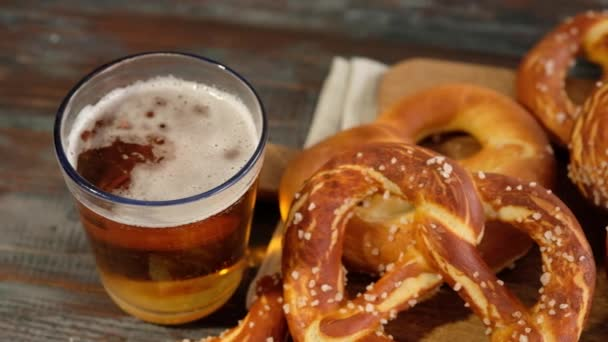 Oktoberfest food menu, soft pretzels and beer on wooden background. Beer is being poured. Misted glass with beer. Slow motion.