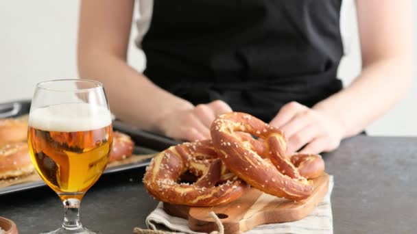 Oktoberfest food menu, soft pretzels and beer on a wooden board and dark background. Beer is poured. Misted glass with beer. Female hands take britzel.