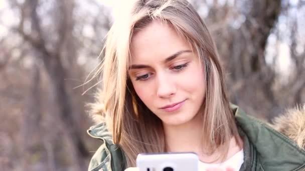 junges und schönes Mädchen mit blonden Haaren hält ein Telefon in der Hand und schreibt eine Nachricht