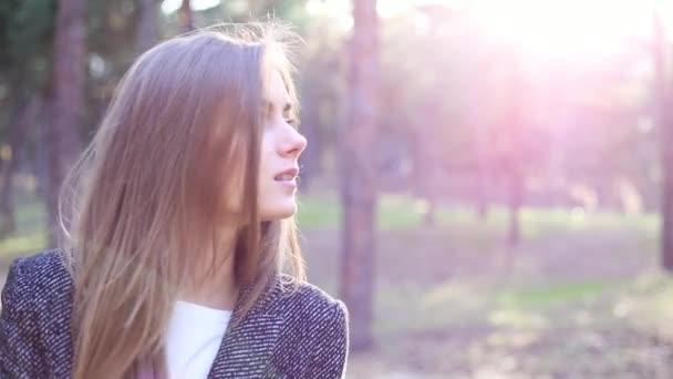 das Mädchen steht im Park, dreht sich um und blickt in die Kamera