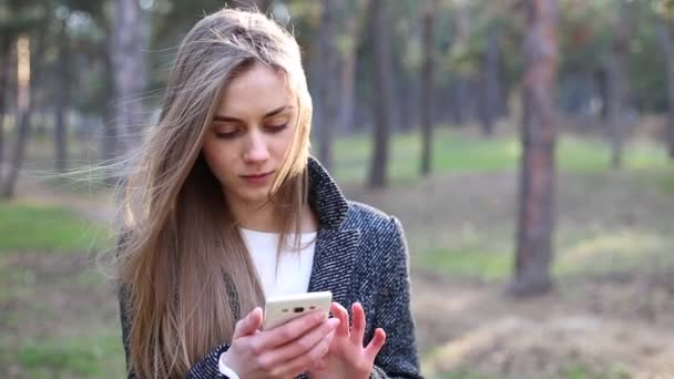 Junge schöne Frau mit blonden Haaren Zifferblatt eine Telefonnummer und nach dem Gespräch auf dem Handy im park