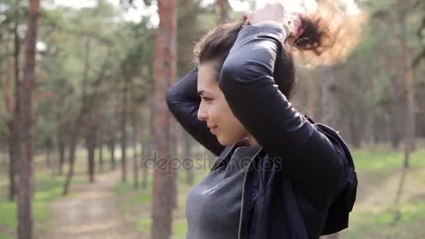 Beautiful brunette woman play with long curly hair in park outdoor.