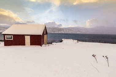 Typical norwegian warm and cosy house located at the lakeside at a fjord in a snowy winter landscape.