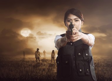 woman with gun against zombies