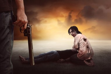 man with gun looking at zombie