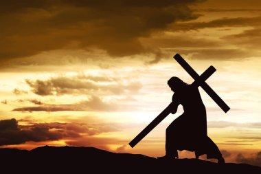 Silhouette of Jesus carry his cross