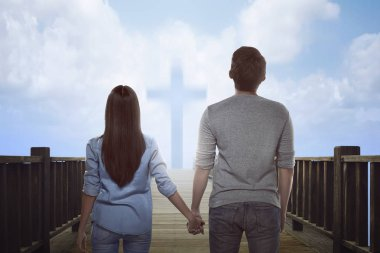 Asian couple looking at bright cross sign