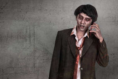 Creepy asian zombie man in suit call via cellphone
