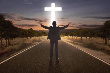 Portrait of man raising hand while praying to god with bright cr