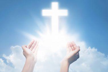 Human hands praying with cross