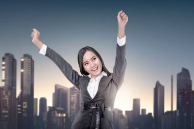 Young asian business woman with raising hands on cityscape background
