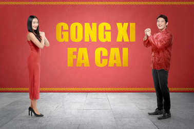 Happy chinese couple in cheogsam clothes with Gong Xi Fa Cai text on red wall background. Happy Chinese New Year