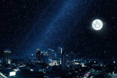 Glowing city with bright moon and many stars in sky at night