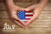 Human hands make a heart shape with american flag inside it. Happy Independence Day