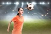 Fényképek Fiatal ázsiai játékos nő címsor focilabdát mező