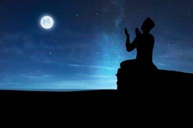 Silhouette of muslim man praying to god at night