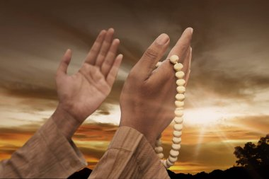 Muslim man praying with prayer beads at sunset