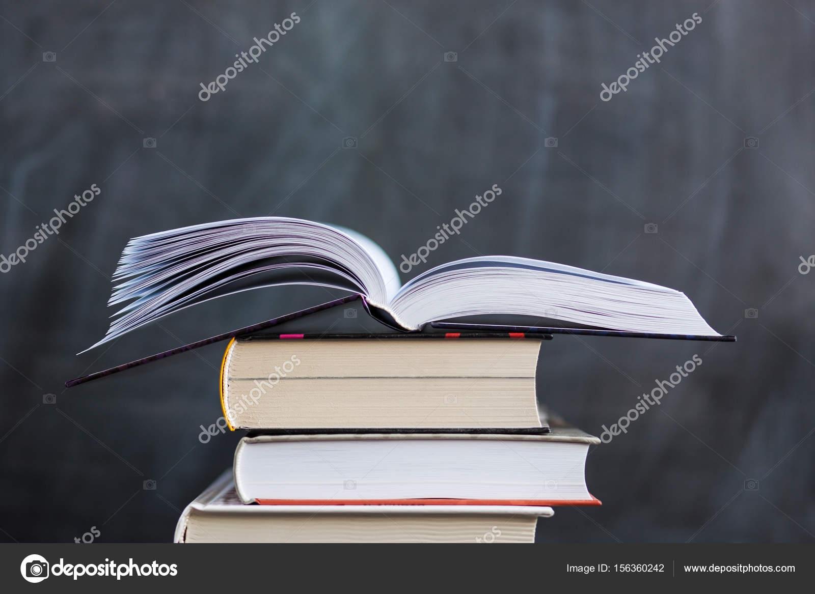 Pile de livres avec tableau noir école en arrière plan un livre i