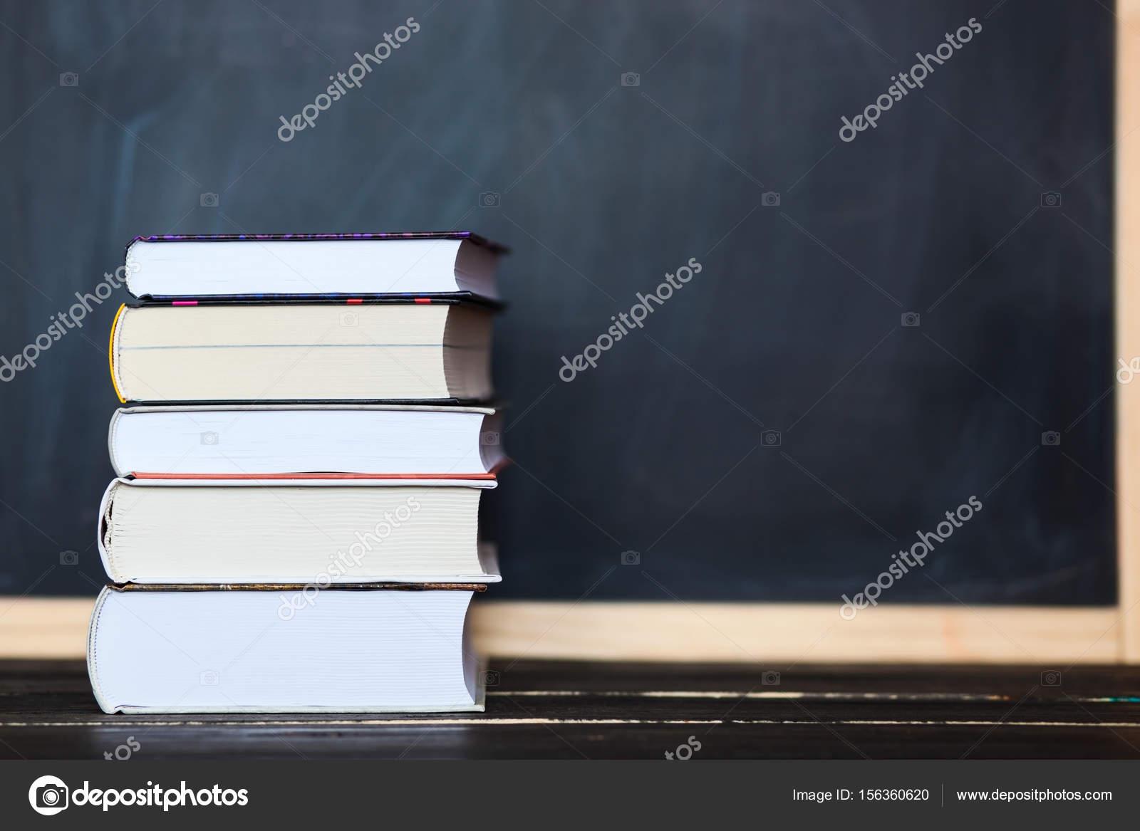 Pile de livres avec tableau noir en arrière plan espace pour
