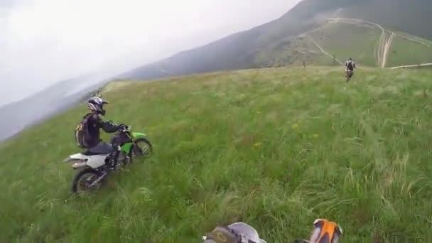 Motorkáři jezdí na štěrkové cestě v horách. Moto motorkář řízení motocyklu na skalnaté silnici.